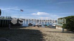 Apparel, Beach, Boardwalk, Boat, Bridge, Building, Clothing, Coast, Countryside, Dock, Flag, Harbor, House, Housing, Nature, Ocean, Outdoors, Pier, Plant, Port, Rural
