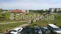 Aerial View, Asphalt, Automobile, Building, Bus, Campus, Car, Coupe, Grass, Housing, Human, Landscape, Nature, Neighborhood, Outdoors, Parking, Parking Lot, Person, Plant, Road