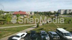 Aerial View, Automobile, Building, Campus, Car, Caravan, Coupe, Grass, Human, Landscape, Nature, Neighborhood, Outdoors, Parking, Parking Lot, Person, Plant, Road