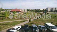 Aerial View, Automobile, Building, Campus, Car, Caravan, Coupe, Grass, Human, Landscape, Nature, Neighborhood, Outdoors, Parking, Parking Lot, Person, Plant, Road, Roof
