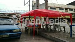 Apparel, Automobile, Awning, Building, Cafe, Cafeteria, Canopy, Car, Chair, City, Clothing, Dirt Road, Flagstone, Food, Food Court, Footwear, Furniture, Gravel, Human, Kiosk, Long Sleeve, Machine, Neighborhood, Pants, Path, Person
