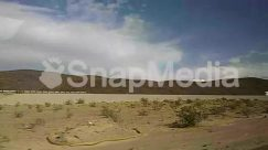 Apparel, Architecture, Automobile, Buggy, Cabin, Car, Cloud, Countryside, Desert, Dune, Field, Grassland, Gravel, Ground, Human, Hut, Land, Landscape, Mountain, Nature, Offroad, Panoramic, Path, Person, Plant, Road, Sand, sky, Slope, Soil, Trailer Truck, Transportation