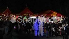 Apparel, Architecture, Bazaar, Carnival, Circus, Clothing, Coat, Column, Costume, Crowd, Halloween, Human, Lab Coat, Leisure Activities, Lighting, Market, Night, Pedestrian, Tent