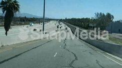 Vehicle,Urban,Town,Street,Road,Pavement,Path,Palm Tree,Overpass,Nature,Human,Highway,Guard Rail,Freeway,City,Car,Building,Bridge,Automobile,Asphalt,Arecaceae,Architecture