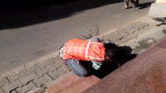 Apparel, Asphalt, Brick, Clothing, Coat, Concrete, Crawling, Denim, Finger, Flagstone, Floor, Footwear, Helmet, Human, Jeans, Machine, Outdoors, Overcoat, Pants, Path, Pavement, Pedestrian, Person