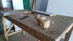 Carpenter, Wood, Plywood, Workshop, Shoe, Footwear, Cup, Coffee Cup, Furniture, Tabletop, Beverage, Drink, Table, Flooring, Milk